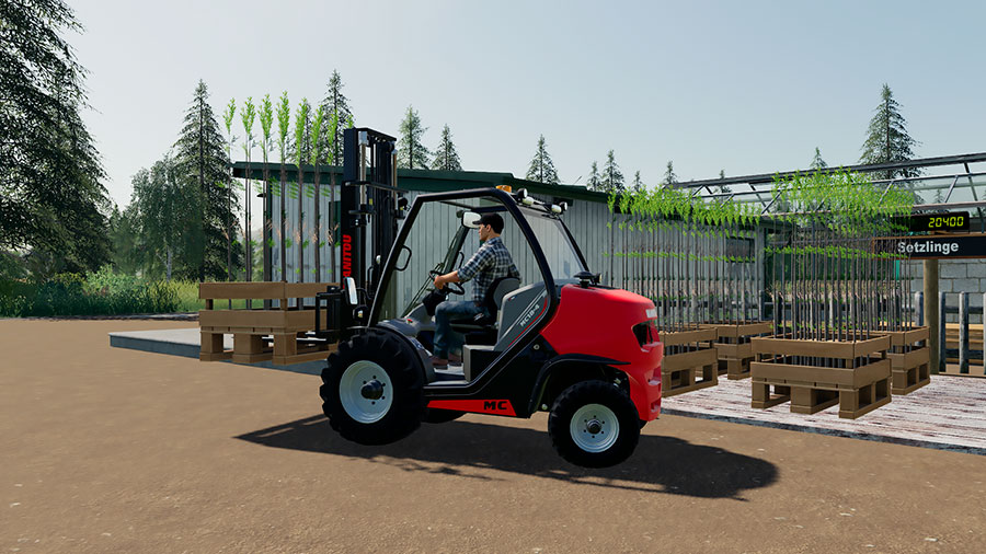 A Manitou forklift is transporting a pallet of tree saplings