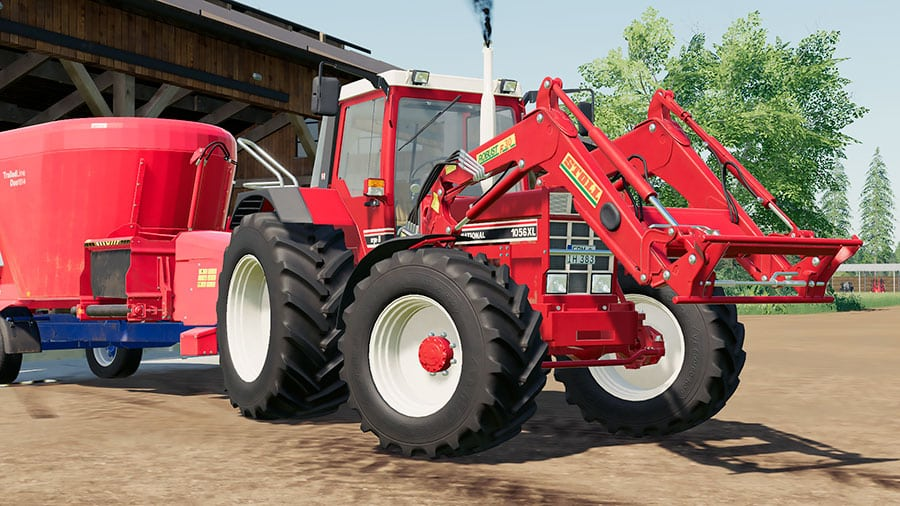 Close up of an International Harvester 1056 XL tractor, with Stoll Robust F30 front loader, pulling a Siloking TMR mixer trailer