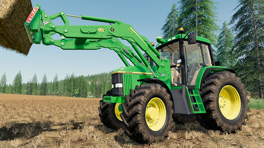 John Deere 6000 Premium with a front loader, lifting a straw bale