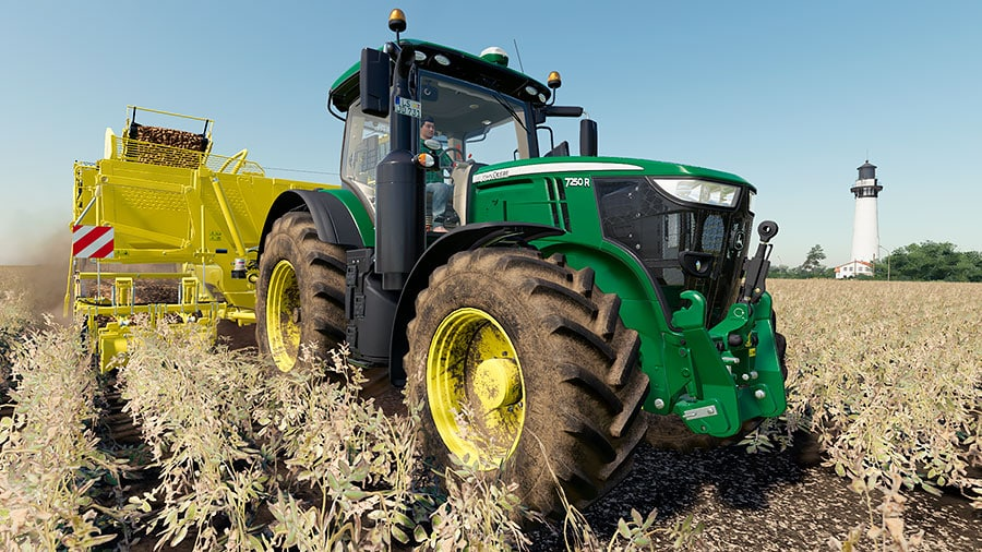 A John Deere 7R, with custom green colors, is pulling a Ropa potato harvester.