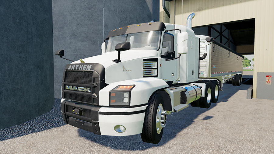 A white Mack Anthem hauling a grain trailer