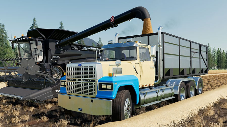 A Ford LTL9000 swap body truck unloading a Fendt Ideal combine harvester