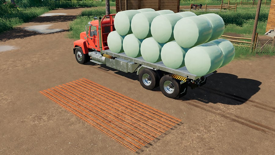 A Mack Pinnacle truck, carrying round bales, is used to demonstrate the unloading marker