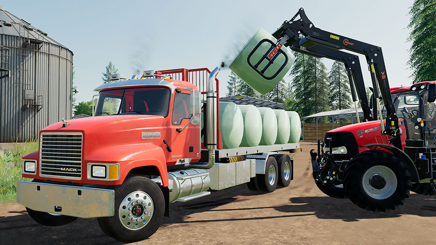 A Mack Pinnacle truck, using the swap body flatbed, is loading round bales in Autoload ligt mode