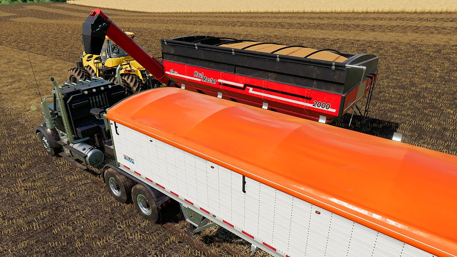 The Wilson trailer about to receive wheat from an Elmer's Haulmaster grain cart